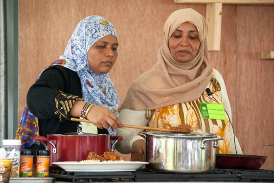 Fatma Ali Busaidy (right) and Amina Harith Swaleh (left), prepare traditional Swahili cuisine from Kenya at the 2014 Smithsonian Folklife Festival.